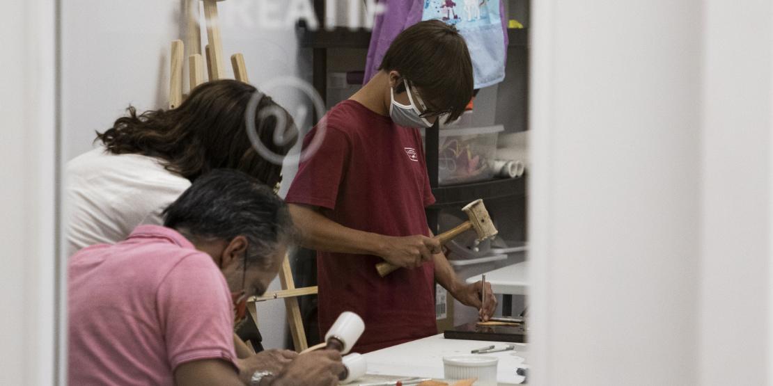 Famille en cours de création lors d'un atelier de fabrication de bracelet de cuir
