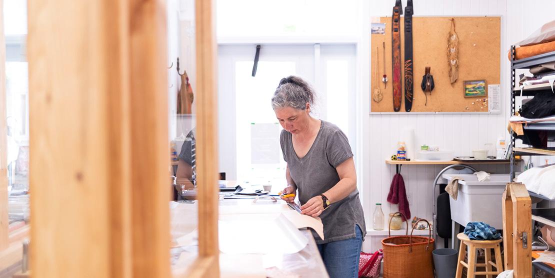 Artiste travaillant le cuir dans un des ateliers du Vivoir