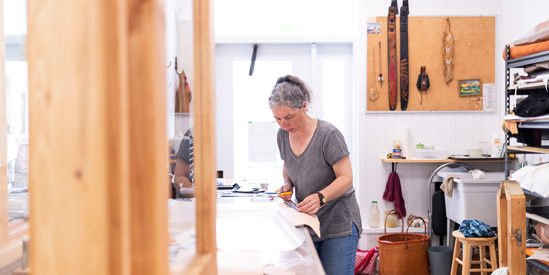 Artist working with leather in one of Le Vivoir's studios